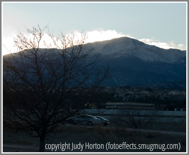 As the sun set, it backlit blowing snow up on Pike's Peak in Colorado Springs, Colorado