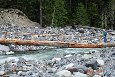 A handmade bridge crossing a creek at the foot of Mt. Ranier