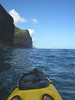 The nose of my kayak, my feet,  and the cliffs of NaPali.