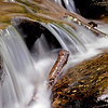 Water flowing over rock and wood