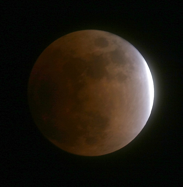BLAINE FALKENA/Staff Photographer<br /> The moon was nearly totally eclipsed at 9:56 Wednesday night causing it to appear a copper color with just a sliver of light left along its right edge as the shadow of the earth moved across it.