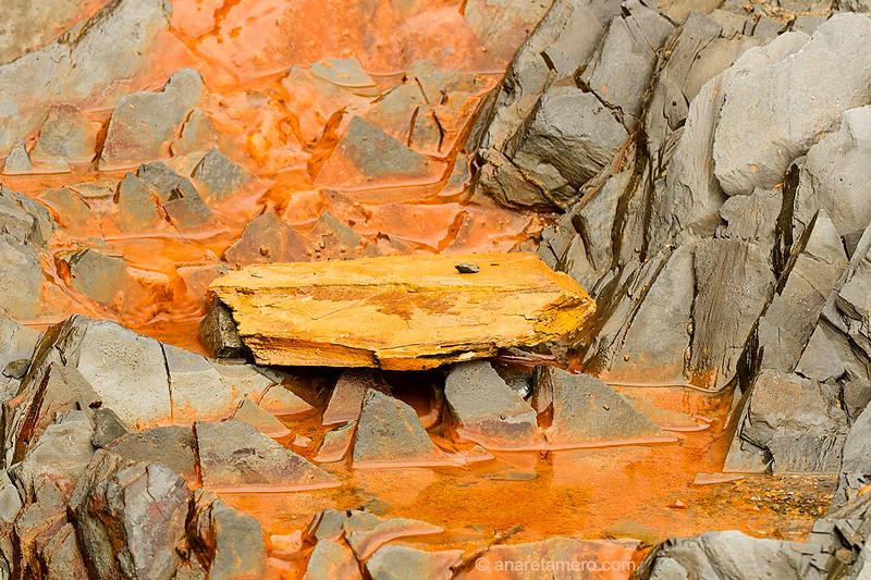 Pequeña fuente férrica en acantilado de pizarra