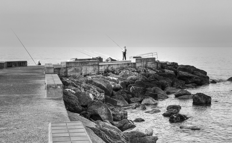 A few fisherman, about 45 minutes before the sun crests the horizon, in Varigotti, Liguria, Italia.