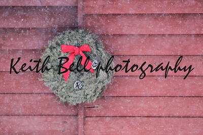 A holiday wreath on the side of a log cabin in a snowstorm.  Reminds me of a Christmas card.