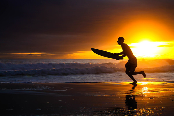 A skim boarder takes to the shore to catch the last few waves before the sun set in Panama City Beach, Florida.