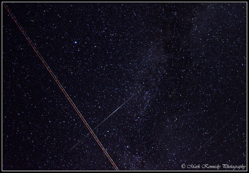 Perseid Meteor passes through the flashing lights trail left by an aircraft. You can also see a satellite in the lower right.