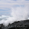 The spray of water from a wave crashing over volcanic rock suspended in mid-air. Photograph taken on Kona, Hawaii.