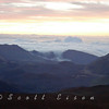 Clouds spilling over the rim of a volcano during a Hawaiian sunrise from 10,000 ft. Photograph taken on Maui, Hawaii