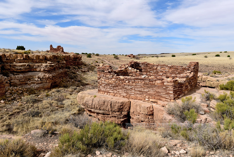 Box Canyon Pueblo ruins in the foreground and to the left 2018.6.6#547. Lomaki pueblo is in the distance. Wupatki Nat. Monument Arizona. See Rock Art and Ancient Ruin Gallery for more Pueblo ruins and cliff dwellings.