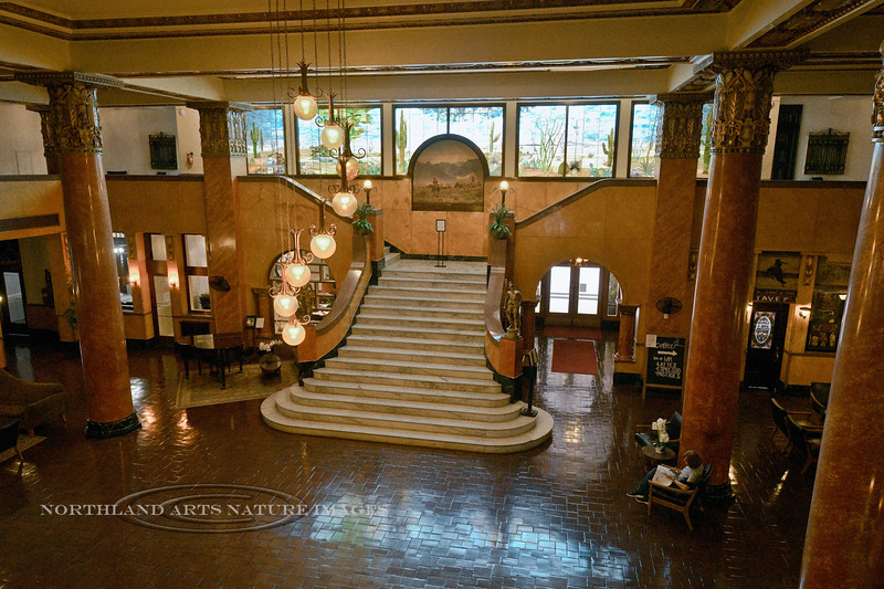 Gadsden Hotel 2019.11.7#4462.2. The lobby of the famous Gadsden Hotel in Douglas Arizona. Panch Villa rode his horse up the marble staircase on one of his raids. The glass murals are Tiffany. The painting at the top of the stairs is a scene in Cave Creek near Portal Arizona by Audley Dean Nicols.
