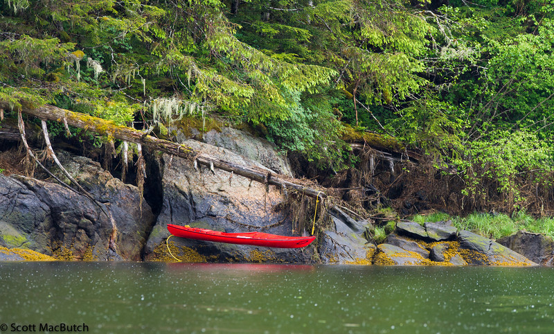 A dropping tide in the rain leaves this sea kayak out of its element.