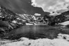 """Snowy Isabelle, Indian Peaks Wilderness CO  This black and white view conveys how barren it is on the wind swept shores of Lake Isabelle in late May.  The far end of the lake is actually still covered in ice.  This is a striking contrast with the late summer view of Isabelle I got <a href=""""http://smu.gs/LGLORG"""">two years ago</a>.  Personally, I wanted to achieve the same reflection results as last time, but I don't mind the windy winter look either.  The hike was much more treacherous this time around, and you can read the story <a href=""""http://smu.gs/KmRSFt"""">here</a>.  As the previous story notes, I only had time to make two different compositions on the shores of Lake Isabelle this time.  The sun was going down, the wind was gusting, clouds were starting to roll in, and I was separated from my group.  I could not linger.  I quickly made two compositions and headed back to the group.  The first composition I shared required HDR, because I included a dark foreground that was in the shadows.  This second composition did not require HDR however, because the bright snowy foreground is not in the shadows.    The black and white conversion is inspired by Ansel Adams.  If you search through Ansel's works you'll find quite a few where he burned in the sky to make it darker.  I tried that technique here, darkening the sky to create an additional contrast against the mountains and to balance out the darkness of the lake.  What do you think?  Daily photo: June 11, 2012, taken May 30, 2012"""