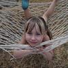 Little girl happily sideways in a hammock on a lazy summer day