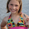 Smiling little girl by a lake with a rotten minnow