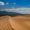 Odd juxtaposition of sand dunes and mountain peaks