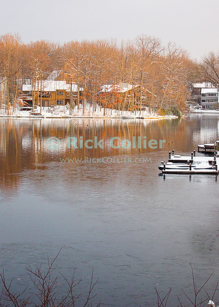 Lake Thoreau, Reston, Virgina, USA.  Snow coats the houses and land as ice begins to crust the lake on a cold winter day.  © Rick Collier<br /> <br /> <br /> Lake Thoreau Reston Virginia USA cold winter ice snow reflection