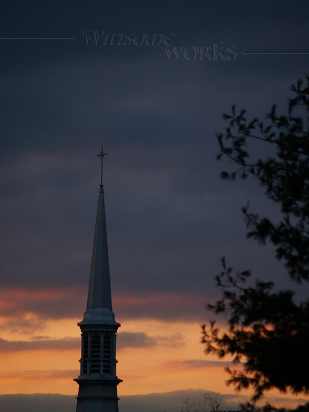 Church steeple in early April sunset with moody sky