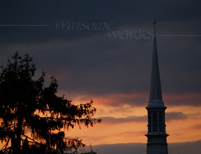 church steeple and fir tree at dusk against colorful moody clouds
