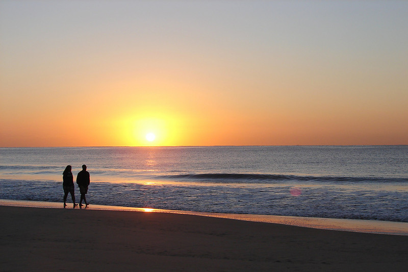 Two people at sunrise on the beach