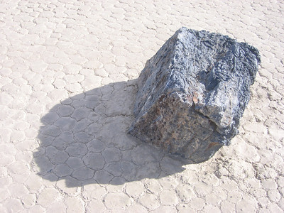 "A rock which has moved; direction is from right to left. There is a dried ""wave"" of mud at the left edge of the rock, and a ""wake"" of dried mud on either side."