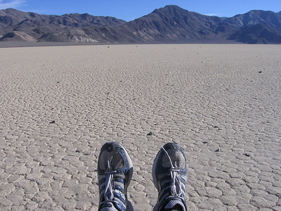 Rock's-eye view (well, minus the shoes) of Racetrack playa, looking east from Grandstand with Cottonwood Mountains in distance.