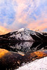 Red sunset reflections portrait of Mount Vaught on Lake McDonald in Glacier National Park.