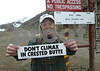 "Executive Director of the High Country Citizens Alliance, Wendy McDermott from Crested Butte, CO holds up a bumper sticker at the gate of the Phelps Dodge Mining Company project just off of Gunnison County Road 12, west side of Crested Butte on Monday, April 5, 2004. McDermott and other citizens are willing to fight for the no mining on the ""Red Lady"" also known as Mount Emmons. (Photo/Nathan Bilow)"