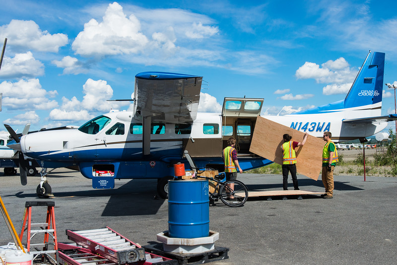 Loading sheet of plywood in Cessna Caravan- Wright Aviation