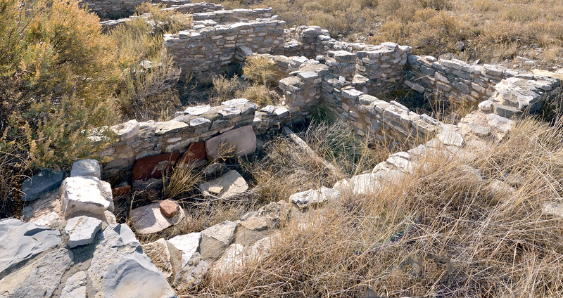 5-NM-2019.11.11#4200.3. Metate's. Three large slab types propped against a wall and two laying on the ground with Mano rocks. These are in the Gran Quivira Ruins, part of the Salinas Pueblo Missions Nat. Monuments near Mountainair New Mexico.