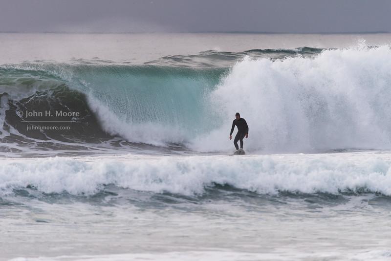 Giant wave crashing behind a surfer at La Jolla Shores.  La Jolla, California, USA.