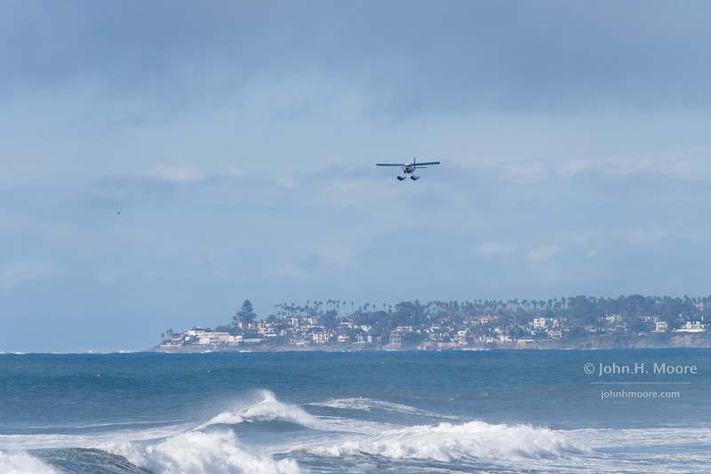 Seaplane approaching Sunset Cliffs in Point Loma, California, USA.