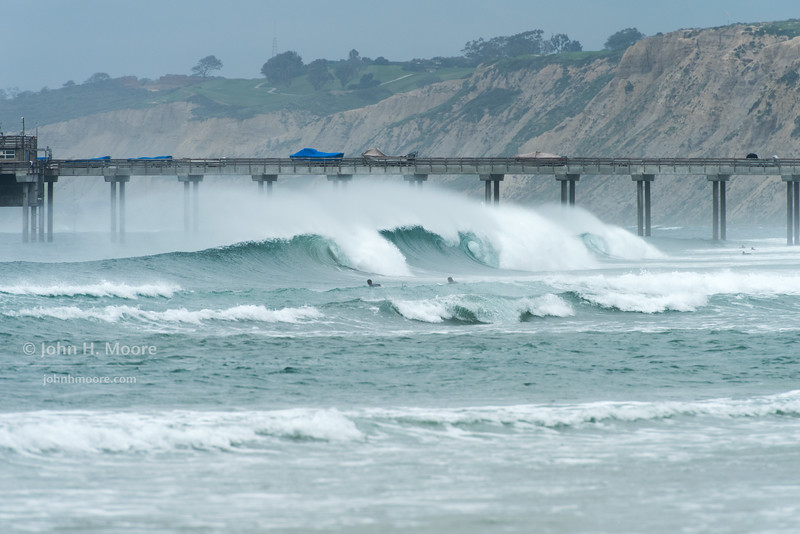 Three surf barrels in a row, with spindrift above, near Scripps Pier in La Jolla, California, USA