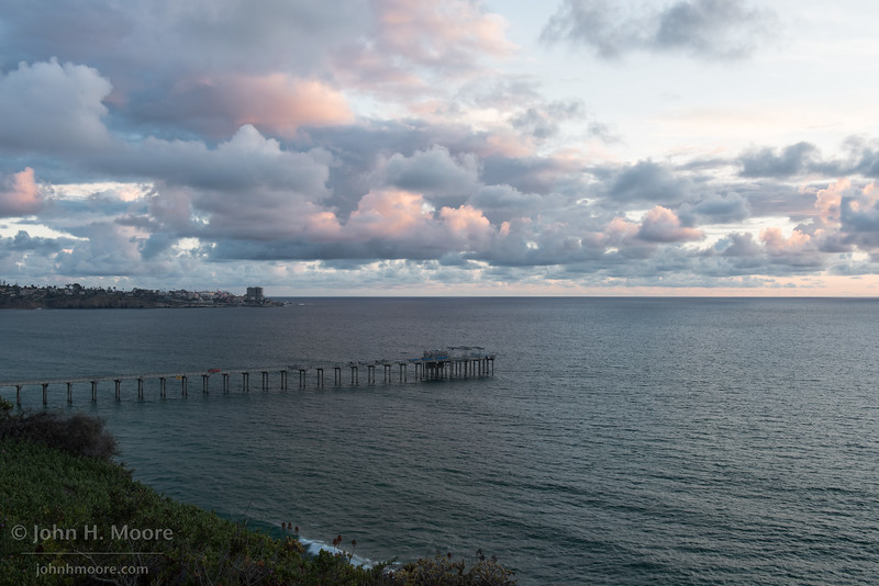 A stormy sunset over Scripps Pier in La Jolla, California, USA.