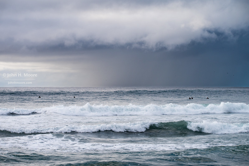 Rain approaches surfers off La Jolla Shores, California, USA.