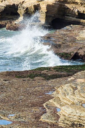 Waves battering against usually covered rocks.
