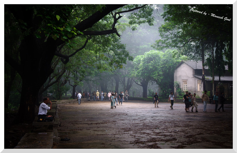Man practising Yoga as morning walkers pass by him on a rainy Sunday morning - Sanjay Gandhi National Park, Mumbai