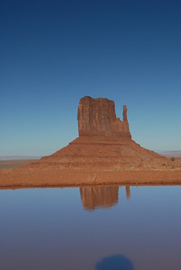 © Joseph Dougherty. All rights reserved.   An ephemeral desert pool briefly reflects the sky and the Mittens monuments after a desert rainstorm in Monument Valley.