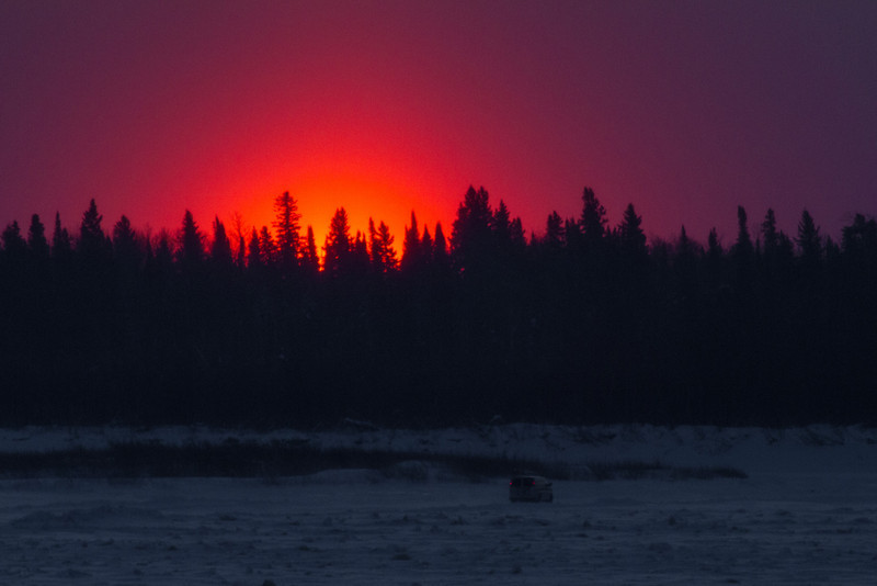 Sunrise over the Moose River seen from Moosonee. Vehicle heads to Moose Factory on ice road across the river.