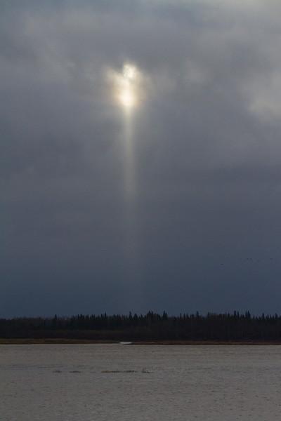 Downward streak of light from a cloud.