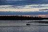 Canoe headed to Moose Factory. Driven by Mike Blueboy. Butler Island in background under colourful skies.