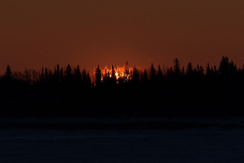 Surnise across the Moose River from Moosonee. Darker exposure. Speck to left of sun is bird.