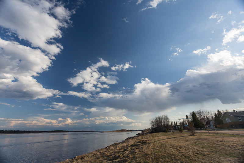 View up Moose River and Revillon Road in Moosonee. Cloudy skies.
