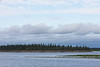 Darker low lying clouds pass over the Moose River at Moosonee, Ontario.