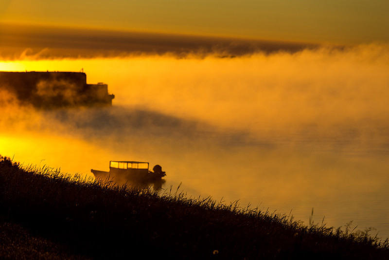 Rising sun burning off fog at Moosonee. Looking down the Moose River. Canoe and barges.