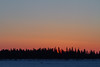 Sunrise over Butler Island in the Moose River. Just a thin band of colour over the trees. Minus 30 windchill minus 40. Truck on the winter road.