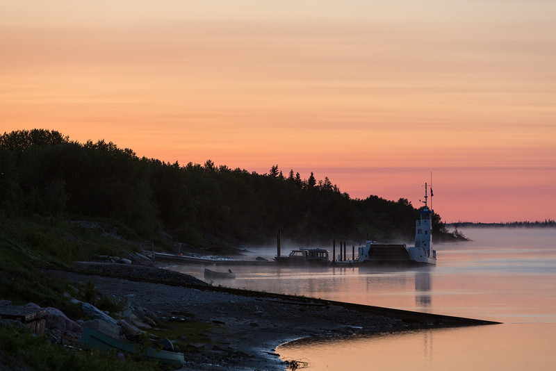 Looking down the Moose River at Moosonee before dawn. Marine railway, barge Niska I and hospital boats at dock.