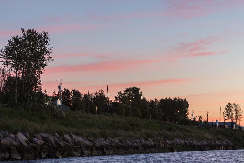 Moose River shoreline in Moosonee under purple clouds before sunrise.