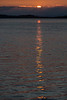 Rising sun reflected in the water of the Moose River.