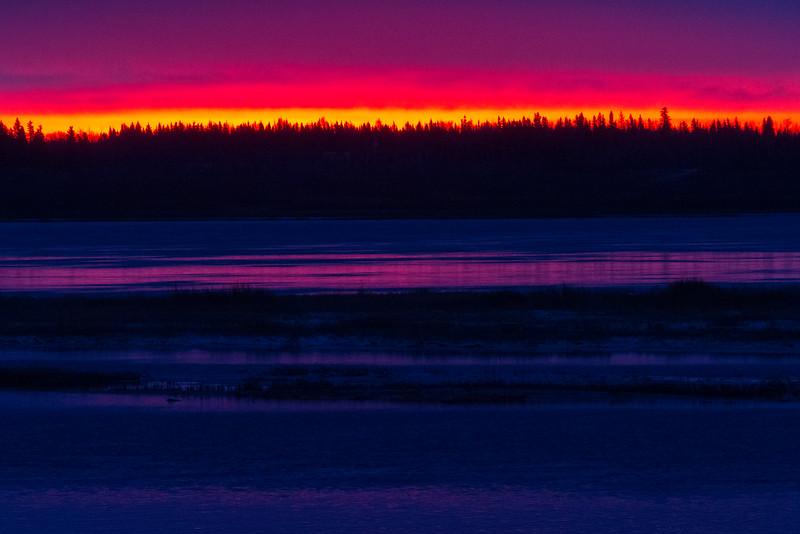 Looking across the Moose River at Moosonee before sunrise. Streak of red along the horizon.