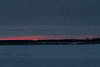 Thin bands of pink low above the horizon. Looking across the Moose River from Moosonee before sunrise. Wider view showing clouds above the colour.